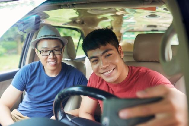 Vrolijke aziatische mannelijke vrienden die samen in auto zitten en selfie nemen Gratis Foto