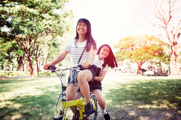 Vrolijke aziatische tiener berijdende fiets in pulbic park Premium Foto