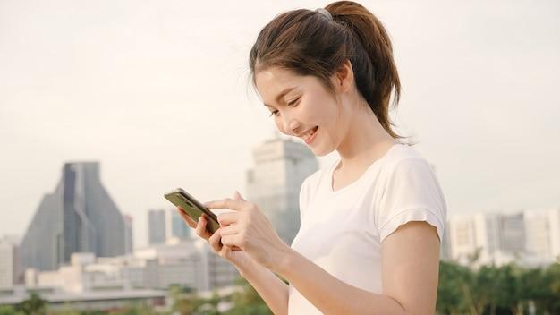 Vrolijke aziatische toeristenblogger vrouw gebruikend smartphone voor richting en kijkend op plaatskaart terwijl het reizen op de straat bij de stad in de stad. Gratis Foto