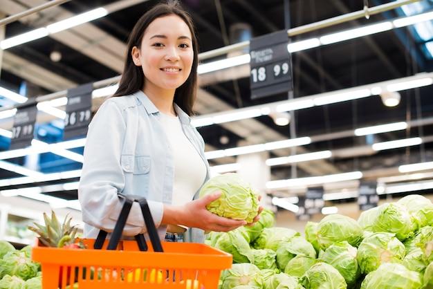Vrolijke aziatische vrouw die kool in markt kiezen Gratis Foto