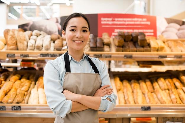 Vrolijke aziatische vrouwelijke bakkerijverkoper met wapens die in supermarkt worden gekruist Gratis Foto