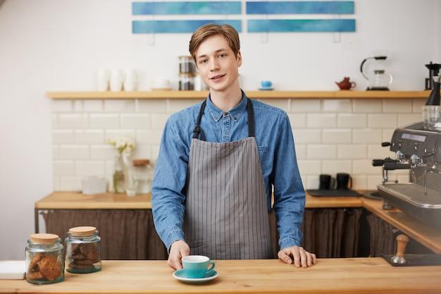 Vrolijke barista bij toog. de klant zijn bestelde koffie geven. Gratis Foto