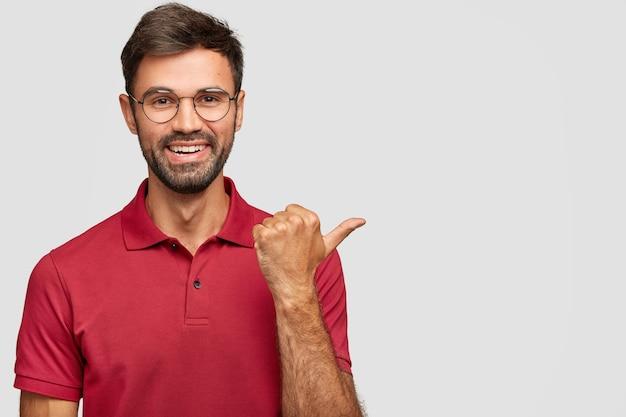 Vrolijke bebaarde blanke man met zachte glimlach, gekleed in vrijetijdskleding, wijst je richting naar mooie plek, wijst met duim opzij Gratis Foto