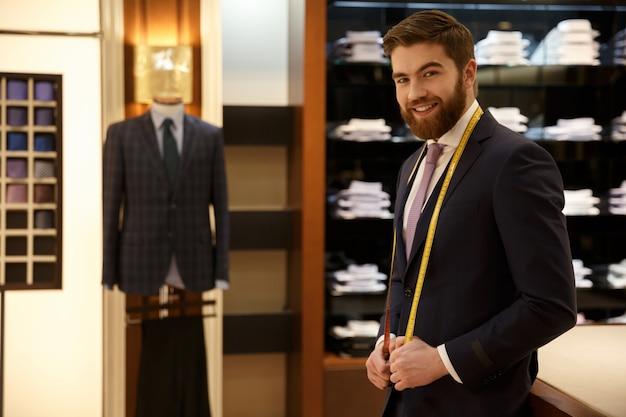 Vrolijke bebaarde man met blauw pak staande met maatregel tape in de kledingkast Gratis Foto