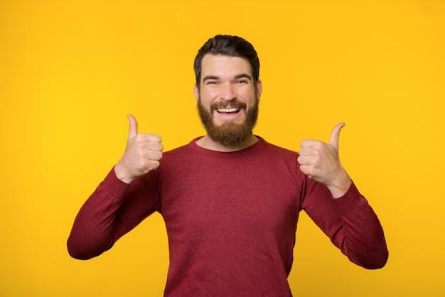 Vrolijke bebaarde man, staande op gele achtergrond en duimen opdagen Premium Foto