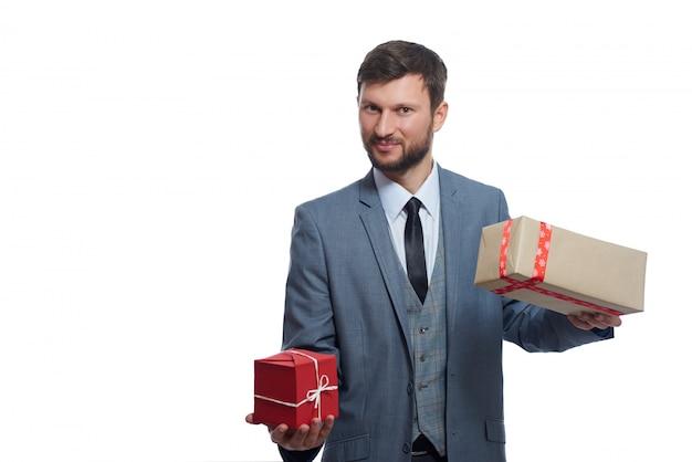 Vrolijke bebaarde zakenman met twee geschenkdozen om te kiezen lachend op wit Gratis Foto