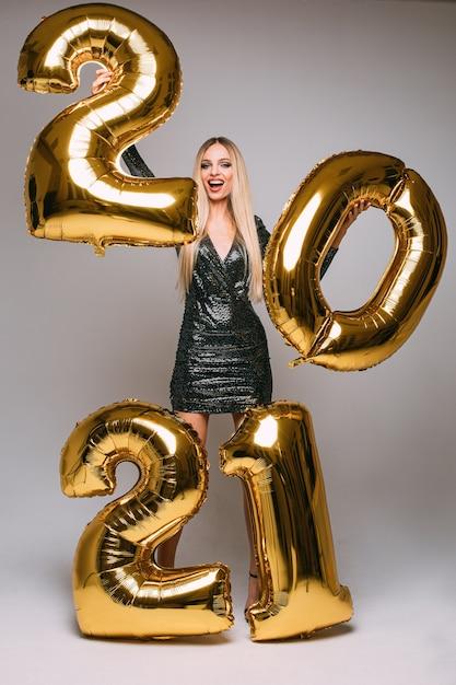 Vrolijke blanke vrouw met lang blond haar viert het nieuwe jaar 2021 Premium Foto