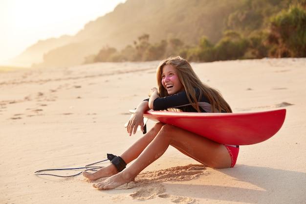 Vrolijke, blije surfer lacht vrolijk als hij wordt geamuseerd door een vriend, heeft een zinkmasker op het gezicht om veilig te kunnen surfen, gebruikt board en riem Gratis Foto