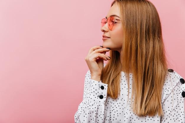 Vrolijke blonde vrouw in roze bril na te denken over iets met een glimlach. aantrekkelijke blanke vrouw ontspannen Gratis Foto