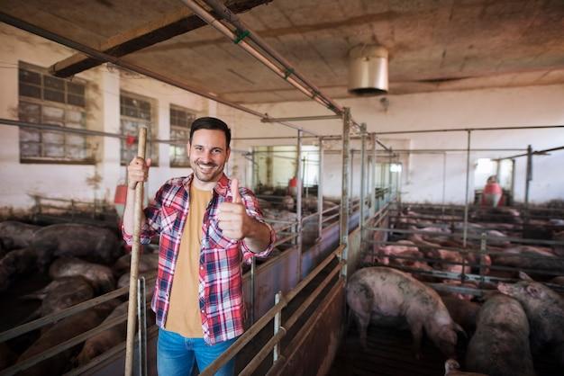 Vrolijke boer met hooivork staande in varkensstal en het verzorgen van varkens huisdieren Gratis Foto