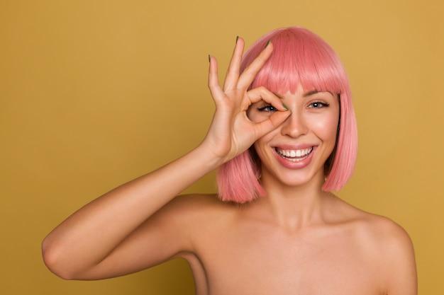 Vrolijke charmante jonge blauwogige rozeharige vrouw met bob kapsel die in een hoge geest is en gelukkig lacht terwijl ze over de mosterdmuur staat met opgeheven ok teken Gratis Foto