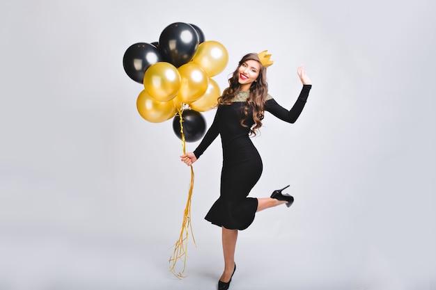 Vrolijke charmante jonge vrouw in luxe elegante mode jurk op hielen nieuwjaar partij vieren op witte ruimte. Gratis Foto