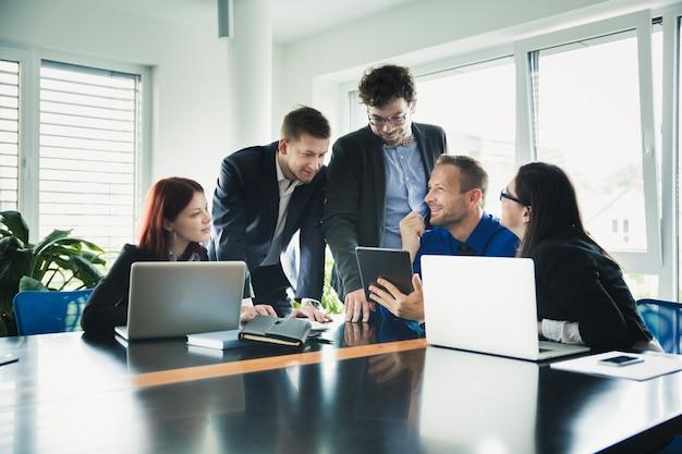 Vrolijke collega's aan tafel met gadgets Gratis Foto