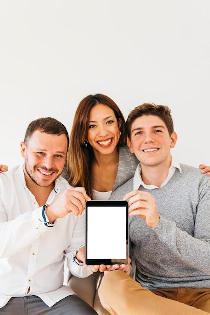 Vrolijke collega's die nieuw apparaat voorstellen Gratis Foto
