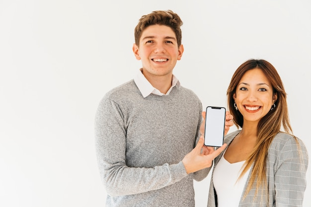 Vrolijke collega's die nieuwe telefoon voorstellen Gratis Foto