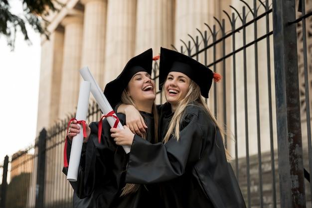 Vrolijke collega's die universiteit een diploma behalen Gratis Foto