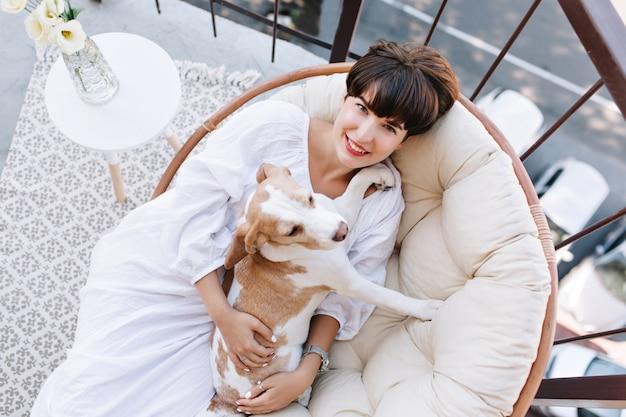 Vrolijke dame in badjas met kort kapsel poseren in stoel met hond zittend in de buurt van vaas met bloemen. Gratis Foto