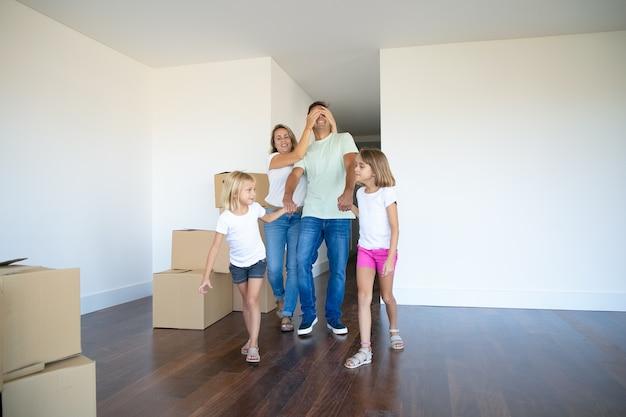 Vrolijke dochters en hun moeder leidt vader met gesloten ogen in hun nieuwe appartement Gratis Foto