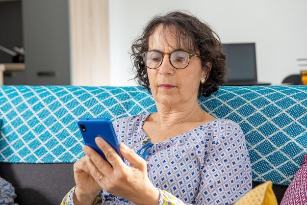 Vrolijke donkerbruine hogere vrouw die smartphone gebruiken terwijl het zitten op bank Premium Foto