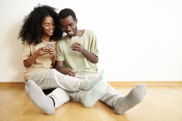 Vrolijke donkere paar genieten van online communicatie, videospelletjes spelen op mobiele telefoons. man in glazen iets op internet tonen aan zijn vriendin Gratis Foto