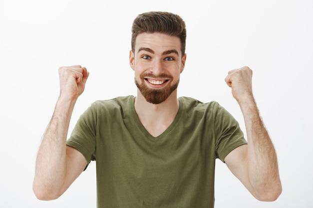 Vrolijke en energieke actieve schattige mannelijke fan met baard in t-shirt gebalde vuisten opheffen in overwinning en triomf vieren overwinning van de eerste prijs glimlachend van opwinding en opgetogen over witte muur Gratis Foto