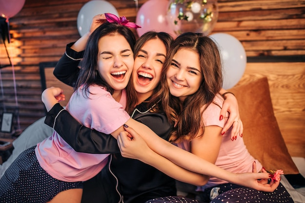 Vrolijke en gelukkige jonge vrouwen die elkaar omhelzen. ze zitten samen op bed in de kamer en kijken. tieners dragen pyjama's. ze hebben een thuisfeest. Premium Foto