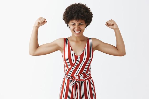 Vrolijke en tevreden knappe afro-amerikaan met krullend kapsel handen opsteken en spieren laten zien die over training gaan, gymresultaten met tevreden glimlach tonen Gratis Foto