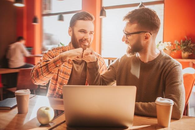 Vrolijke en vrolijke hipsters zitten aan tafel in café en zetten hun vuisten samen. het is een goede dag voor hen. Premium Foto