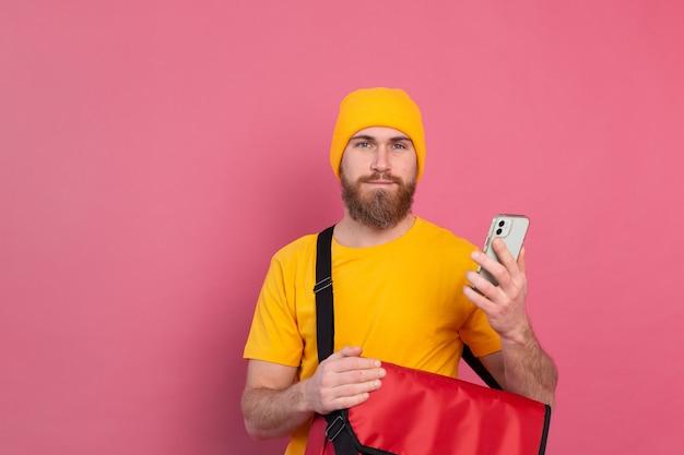 Vrolijke europese bezorger met tas casual hold telefoon op roze Gratis Foto