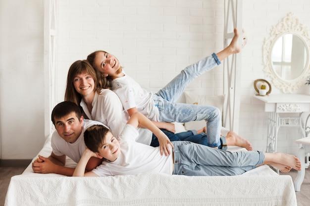 Vrolijke familie die op bed ligt dat camera bekijkt Premium Foto