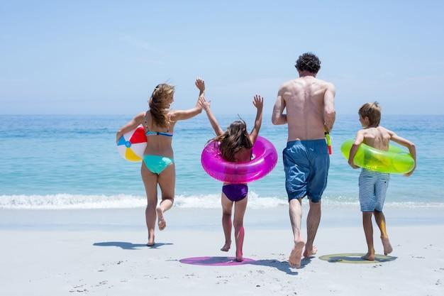 Vrolijke familie loopt naar zee met zwemuitrusting Premium Foto