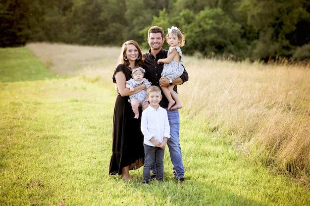Vrolijke familie met hun kinderen en een pasgeboren baby staande op een grasveld Gratis Foto