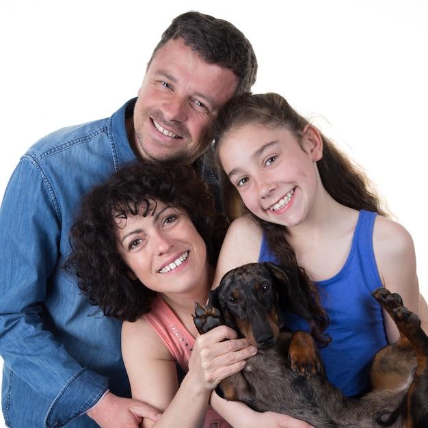 Vrolijke familie met jong geïsoleerd meisje en haar hond Premium Foto