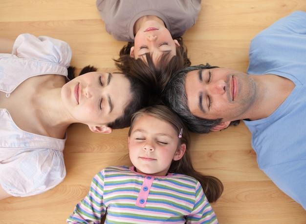 Vrolijke familieslaap die op de vloer liggen Premium Foto