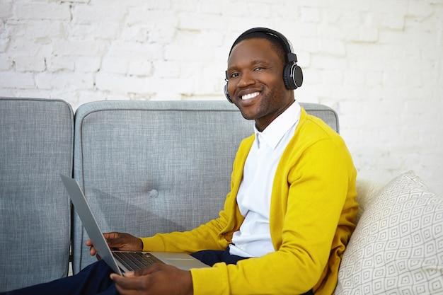 Vrolijke gelukkig jonge african american man in vrijetijdskleding genieten van moderne elektronische apparaten thuis, luisteren naar favoriete muziek met behulp van draadloze hoofdtelefoons en laptopcomputer, ontspannen op de bank Gratis Foto