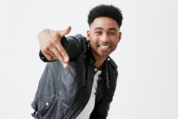 Vrolijke gelukkige jonge donkere man met afro kapsel in casual stijlvolle kleding glimlachend met tanden, pistool gebaar in de camera tonen, dansen, plezier maken op het verjaardagsfeestje van een vriend. Gratis Foto