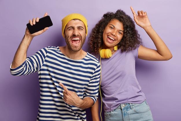Vrolijke gemengde race jonge vrouw en man hebben plezier en dans, luister naar muziek via de mobiele telefoontoepassing, draag een koptelefoon, gekleed in vrijetijdskleding Gratis Foto