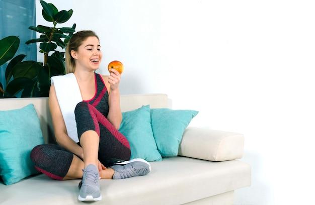 Vrolijke gezonde jonge vrouw zittend op de bank kijken naar rode appel Gratis Foto