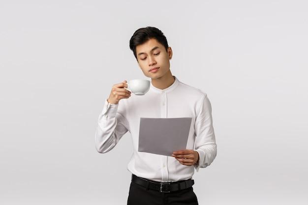 Vrolijke glimlachende aziatische jonge ondernemer met de witte documenten van de overhemdsholding en het drinken van koffie Premium Foto