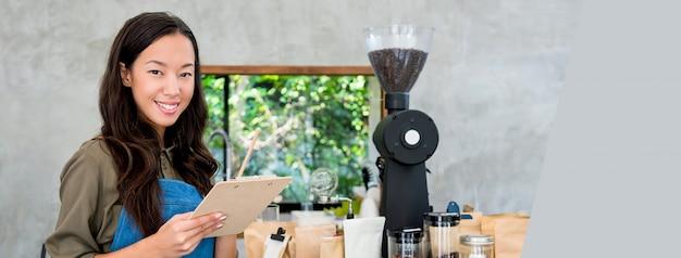 Vrolijke glimlachende jonge aziatische vrouwenondernemer bij koffiewinkel tegen Premium Foto