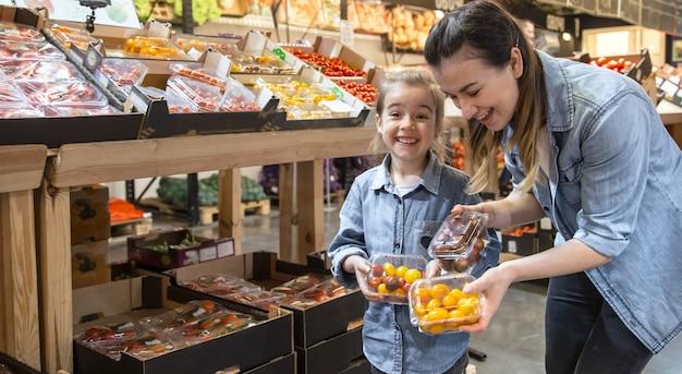 Vrolijke glimlachende jonge vrouw met weinig dochter het kopen boltomaten bij de markt Gratis Foto