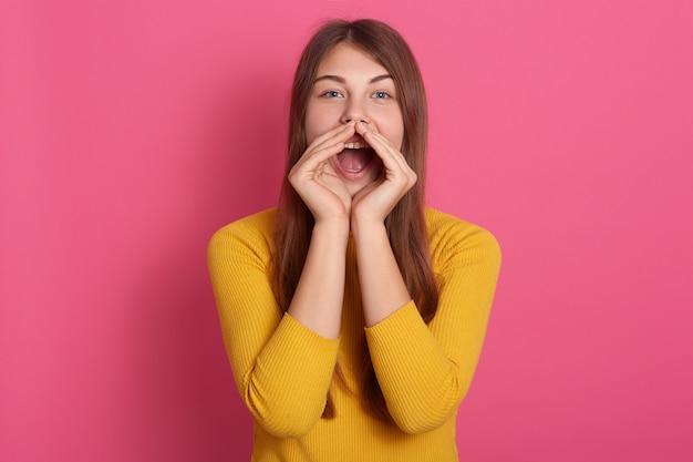 Vrolijke grappige jonge vrouw, gekleed in gele trui schreeuwen met handgebaar in de buurt van mond geïsoleerd over roze muur, dame met lang haar Gratis Foto