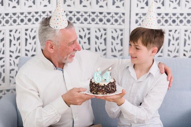 Vrolijke grootvader en kleinzoon die elkaar bekijken terwijl het houden van heerlijke cake met kaars Gratis Foto