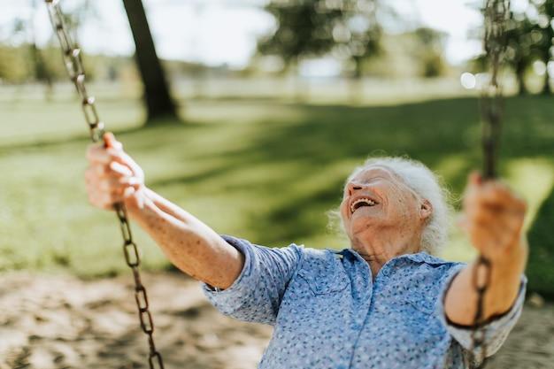 Vrolijke hogere vrouw op een schommeling bij een speelplaats Premium Foto
