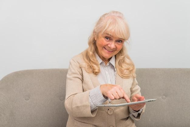 Vrolijke hogere vrouw wat betreft het digitale tabletscherm met vinger Gratis Foto