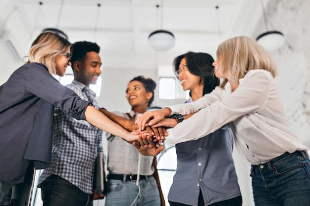 Vrolijke internationale studenten met een blij gezicht gaan samenwerken aan een wetenschappelijk project. indoor foto van blonde vrouw in trendy blouse hand in hand met collega's. Gratis Foto