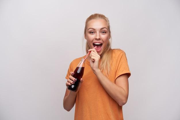 Vrolijke jonge aantrekkelijke blonde vrouw met paardenstaart kapsel gelukkig kijken camera met brede mond geopend en fles frisdrank houden in opgeheven handen, geïsoleerd op witte achtergrond Gratis Foto