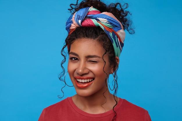 Vrolijke jonge aantrekkelijke brunette krullende vrouw met feestelijke make-up vrolijk knipogen naar de voorkant terwijl ze graag glimlacht, staande over de blauwe muur in gekleurde kleding Gratis Foto