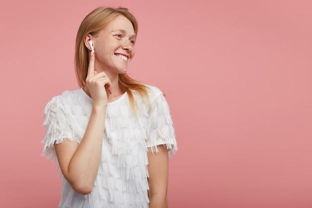 Vrolijke jonge aantrekkelijke dame met foxy haar oortje invoegen in haar oor en positief opzij kijken met een brede, gelukkige glimlach, gekleed in wit elegant t-shirt terwijl staande op roze achtergrond Gratis Foto