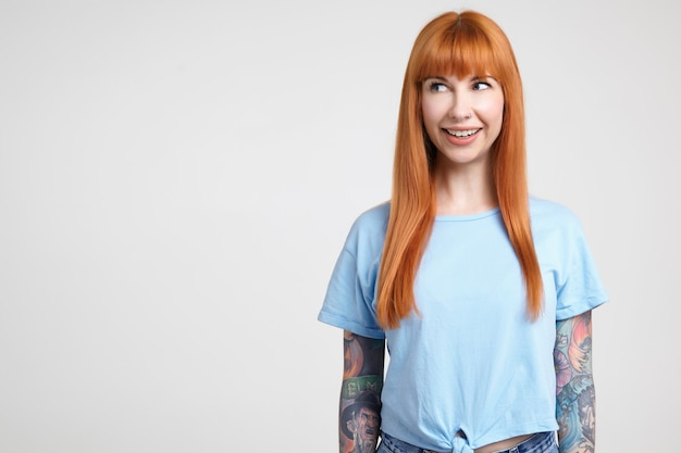 Vrolijke jonge aantrekkelijke langharige roodharige dame met casual kapsel glimlachend wijd terwijl ze graag opzij kijkt, poseren op witte achtergrond in blauw t-shirt Gratis Foto